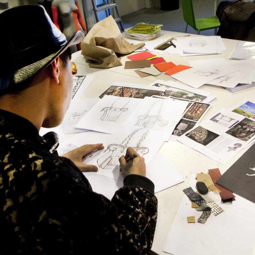 Etudiant en train de dessiner un sac à main à l'Institut Français de la Mode