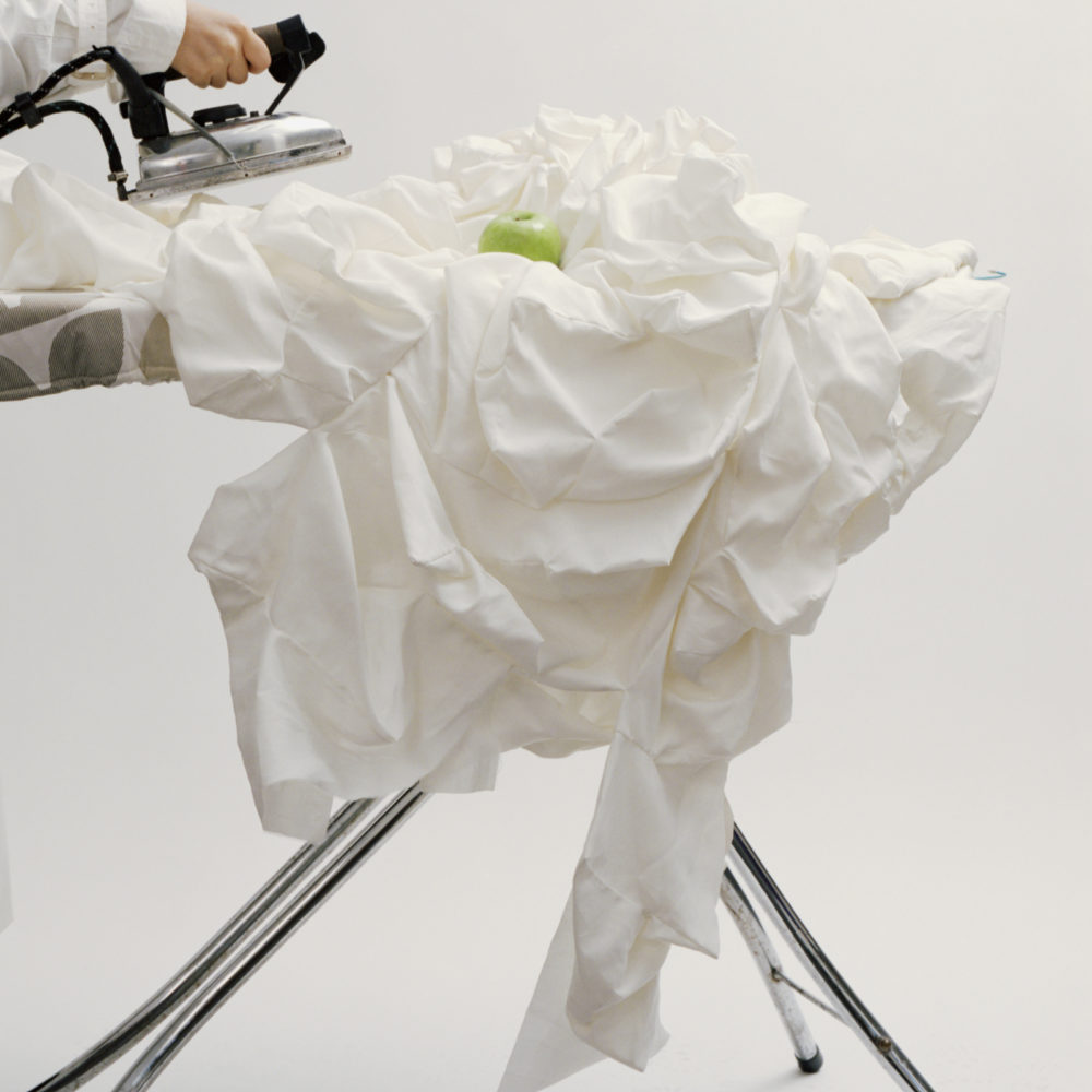 Crumpled fabric being ironed