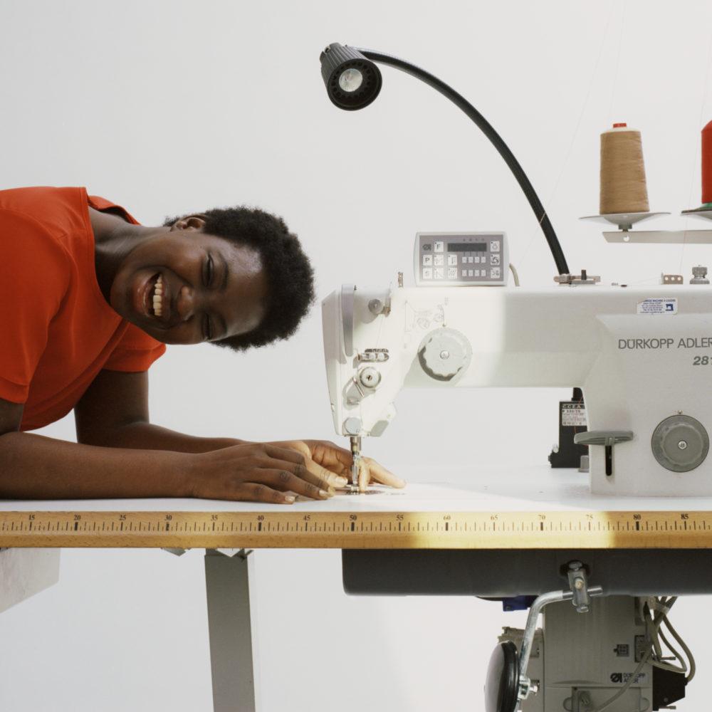 Photographie représentant une étudiante près d'une machine à coudre pour illustrer le programme Bachelor en Modélisme